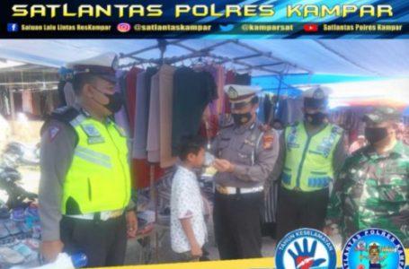 Kasat Lantas Polres Kampar Bagikan Masker di Pasar Air Tiris dan Imbau Warga Patuhi Prokes